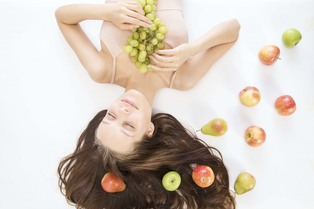 Girl lying down with fresh fruits for skin care | Keeping Your Skin Smooth and Glowing Even on Lockdown| Karlaroundtheworld.com